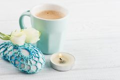 Blue cup of coffee with paperweight. Blue cup of coffee with crochet paperweight on white wooden table with lit candle Royalty Free Stock Image