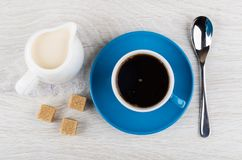 Blue cup with coffee, spoon, jug of milk, brown sugar. On wooden table. Top view Royalty Free Stock Photography