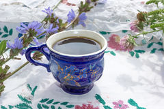 Blue cup of coffee tea chicory drink with chicory flower,  hot beverage on embroidered fabric background Stock Photos