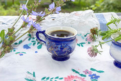 Blue cup of coffee tea chicory drink with chicory flower,  hot beverage on embroidered fabric background Royalty Free Stock Photography