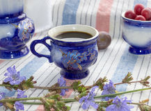 Blue cup of coffee tea chicory drink with chicory flower,  hot beverage on embroidered fabric background Royalty Free Stock Photos