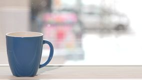 Blue cup of coffee tea hot drink stand on window sill and snow fall outdoor stock video