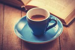 Blue cup of the coffee and vintage book. Stock Photos