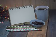 Open notebook and a cup of coffee on the tablenn Royalty Free Stock Image