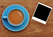 Blue cup of hot coffee and old paper photo frame. On wood table Royalty Free Stock Photo