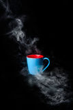 Blue Cup of hot coffee surrounded in steam black background Royalty Free Stock Photo