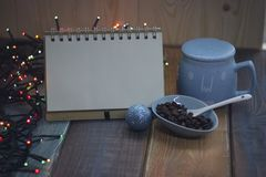 Open notebook, blue cup and coffee beans on Christmas tablen Royalty Free Stock Photos