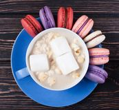 Blue cup with macaroons on wood royalty free stock image