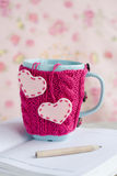 Blue cup in pink sweater with felt hearts standing on notebook Stock Photo