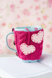 Blue cup in pink sweater with felt hearts standing on an notebook Royalty Free Stock Photos