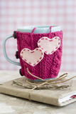 Blue cup in pink sweater with hearts standing on notebook Royalty Free Stock Image