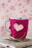 Blue cup in a pink sweater standing on an  notebook Stock Photography