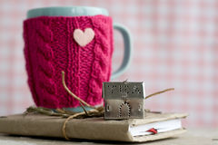 Blue cup in a pink sweater standing on an old notebook Stock Image