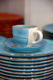 Blue cup and saucer with plates. There is a blue with white service: cup, saucer and some plates Stock Photography