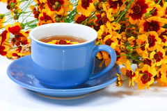 Blue cup of tea with flowers Royalty Free Stock Photo