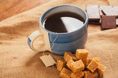 Blue cup of tea and lump sugar on sacking background Stock Photos