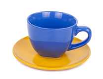 Blue cup of tea on a yellow saucer Stock Image