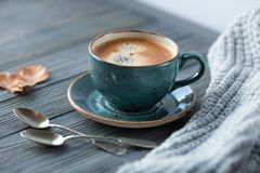 Blue cup whith coffee, knitted sweater, autumn leaves on wooden background. stock photos