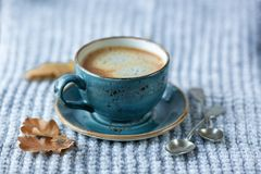 Blue cup whith coffee, knitted sweater, autumn leaves on wooden stock photos