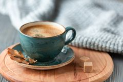 Blue cup whith coffee, knitted sweater, autumn leaves on wooden background. stock photo