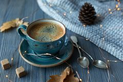 Blue cup whith coffee, knitted sweater, autumn leaves on wooden background. royalty free stock photography