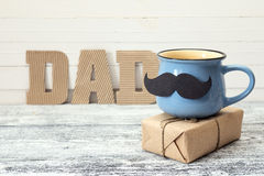 Blue Cup With A Mustache, Gift Box And An Inscription Dad In The Royalty Free Stock Images