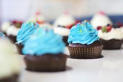 Blue cupcakes with sprinkles on white table Royalty Free Stock Image