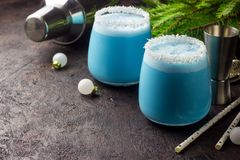 Blue curacao Christmas Cocktail, garnished with coconut on Christmas decorated holiday table with Christmas ornaments. Holiday. Cocktails with ice Blue Curacao royalty free stock image