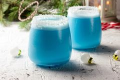 Blue curacao Christmas Cocktail, garnished with coconut on Christmas decorated holiday table with Christmas ornaments. Holiday. Cocktails with ice Blue Curacao royalty free stock images
