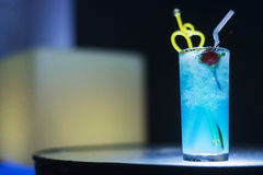 Blue curacao cocktail drink with cherry at night Stock Images