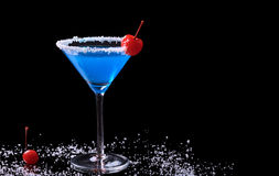 Blue Curacao with Coconut and Maraschino Cherry. Blue Curacao drink in a glass with coconut flake rim and a maraschino cherry surrounded by coconut flakes and a Royalty Free Stock Photography