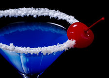 Blue Curacao with Coconut and Maraschino Cherry. Blue Curacao with coco flakes on the glass rim and garnished with a red maraschino cherry photographed on black Royalty Free Stock Photos
