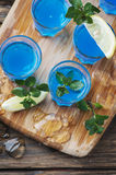 Blue curacao liqueur with lemon on the wooden table Royalty Free Stock Photography
