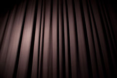 Blue Curtain. Heavy dark blue curtain with background texture and copy space. Angled view. Spotlight creating natural vignette stock image