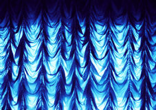 Blue curtain. A blue shining curtain on the wall Stock Photo