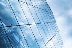 Blue curtain wall made of toned glass. And steel constructions under cloudy sky Stock Image