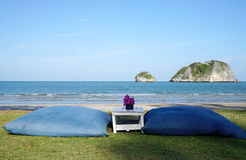 Blue cushions on the lawn with beautiful beach background Stock Photography