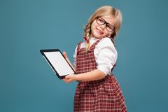 Cute little girl in red dress, white shirt and glasses holds empty tablet royalty free stock photos