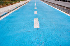 Blue cycle path along the coast Stock Photos