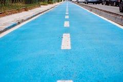 Blue cycle path along the coast Stock Photos