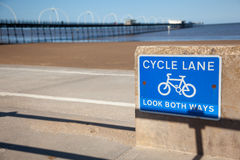 Blue cycle path lane sign by beach Stock Images