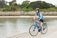 Blue cyclist on shoreline Royalty Free Stock Photos
