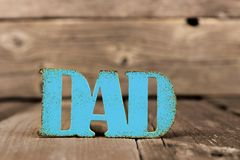 Blue DAD distressed metallic sign against rustic wood. Blue DAD distressed metallic sign against a rustic wood background Stock Photography