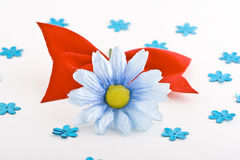 Blue daisy with bow. A blue gerbera and a bow on a white background, surrounded by small daisy cutouts Royalty Free Stock Photo