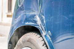 Blue damaged car in crash accident with scratched paint and dented rear bumper metal body, close up selective focus.  Stock Photo