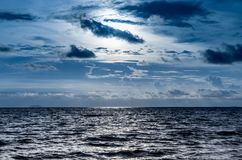 Blue dark dramatic sky shining ocean. Blue dark dramatic sky with shining ocean royalty free stock images