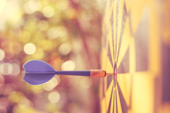 Blue dart arrow in the center of dartboard. Blur and bokeh. Close up blue dart arrow in the center of dartboard. Blur and bokeh in sunrise time background. Warm Royalty Free Stock Image
