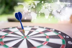 Blue dart arrow hitting in the target center of dartboard with g Royalty Free Stock Image