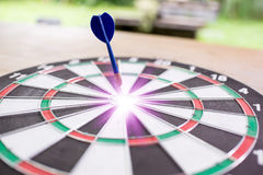 Blue dart arrow hitting in the target center of dartboard with g Stock Photos