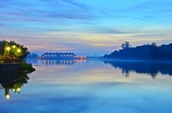 Blue Dawn Sunrise. A misty blue dawn casts its reflection on the river while a man photographs the scenery Stock Image